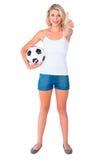 Fan de futebol louro bonito que guarda a bola que mostra os polegares acima Imagens de Stock