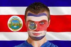 Fan de futebol novo sério na pintura da cara imagem de stock royalty free