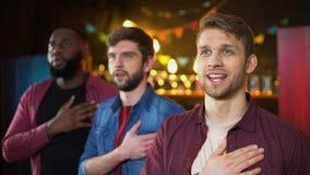 Fan de futebol patrióticos que escutam o hino e que abraçam, jogo de observação na barra video estoque