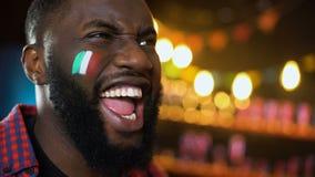 Fan de futebol preto extremamente emocional com a bandeira italiana na gritaria do mordente, objetivo video estoque