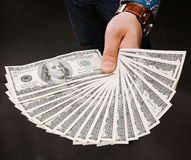 Fan dei soldi della tenuta della mano Cento banconote in dollari su un fondo grigio Banconota, primo piano L'offerta di un dono Fotografia Stock Libera da Diritti