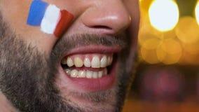 Fan del hombre con la bandera francesa pintada en mejilla que anima emocionalmente para el equipo nacional metrajes