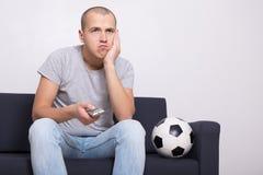 Fan di calcio annoiato con il gioco di sorveglianza della palla sulla TV Fotografia Stock Libera da Diritti