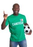 Fan di calcio felice dal Camerun con la palla Immagini Stock