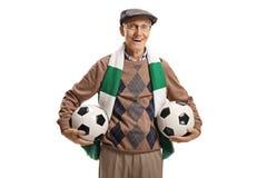 Fan di calcio senior che tiene due palloni da calcio fotografie stock