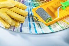 Fan di pantone dei guanti di sicurezza del vassoio del rullo di pittura su fondo bianco immagini stock