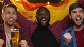 Fan di sport con la bandiera spagnola che incoraggiano per la squadra nazionale, gioco di sorveglianza in pub video d archivio