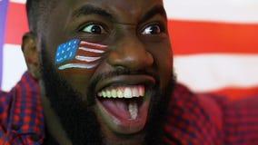 Fan di sport nero che ondeggia la bandiera di U.S.A. che si rallegra vittoria favorita del gruppo, campionato stock footage