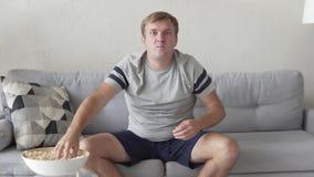 Fan divertida con palomitas en casa en el sofá almacen de metraje de vídeo