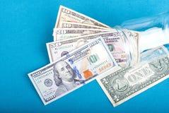Fan of dollar bills in a glass jar near a dollar, top view, blue Stock Image