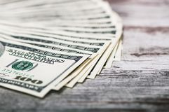 A fan of 100 dollar bills. On wooden background Stock Images