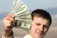 Fan of dollars in hand and man's face. Man holding dolllars in hand, face is defocused stock image