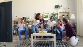 Fan emozionali che guardano gli sport sulla TV che esprime fare di emozioni alto--cinque archivi video