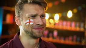 Fan with english flag painted on cheek unhappy with team losing match, failure. Stock footage stock footage