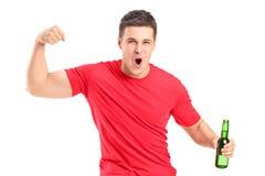 Fan euforico che tiene una bottiglia di birra ed incoraggiare immagine stock