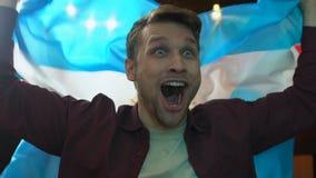 Fan extremadamente alegre que agita la bandera de la Argentina en la barra que disfruta meta del equipo nacional metrajes