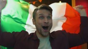 Fan extremadamente alegre que agita la bandera italiana en la barra, victoria del equipo nacional que disfruta metrajes