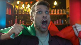 Fan extremadamente feliz que agita la bandera portuguesa en la barra, victoria del equipo de deportes que disfruta almacen de video