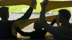 Fan family with boy waving scarves in support of football team, weekend activity. Stock footage stock footage