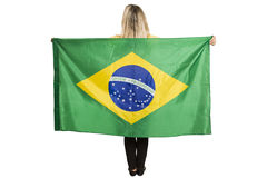 Fan femelle heureuse avec le drapeau brésilien tenant un ballon de football image stock