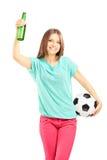 Fan femenina feliz que sostiene un balón de fútbol y una botella de cerveza Imagen de archivo