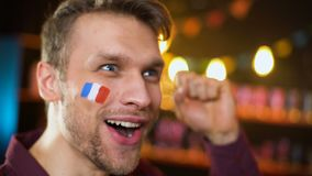 Fan francés alegre con la bandera pintada que celebra la victoria del equipo, haciendo sí gesto metrajes