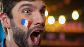 Fan francés barbudo hermoso feliz con la bandera pintada en mejilla que celebra meta metrajes