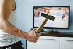 Fan with a hammer watching the loss of his favorite team. At the world hockey championship. an excited fan is rooting for his favorite team. losing in a hockey Royalty Free Stock Image