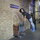 Fan of Harry Potter recreates pushing a trolley towards platform nine and three quarters from the film. LONDON, ENGLAND - JULY 12, 2016 Fan of Harry Potter Royalty Free Stock Photography