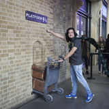 Fan of Harry Potter recreates pushing a trolley towards platform nine and three quarters from the film. LONDON, ENGLAND - JULY 12, 2016 Fan of Harry Potter Royalty Free Stock Image