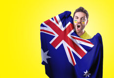 Fan holding the flag of Australia on yellow background Royalty Free Stock Photos