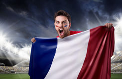 Fan holding the flag of France in the stadium royalty free stock photography