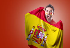 Fan holding the flag of Spain on red background Stock Photo