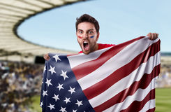 Fan holding the flag of USA in the stadium Stock Image