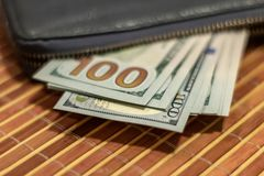 Fan hundred dollar bills in a black wallet royalty free stock image