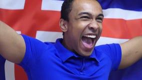Fan islandais célébrant tout en tenant le drapeau de l'Islande dans le mouvement lent banque de vidéos