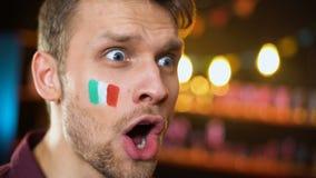 Fan italiano alegre con la bandera pintada en mejilla que grita, meta que anota del equipo almacen de metraje de vídeo