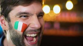 Fan italiano alegre con la bandera pintada en mejilla que grita, meta que anota del equipo, triunfo almacen de video