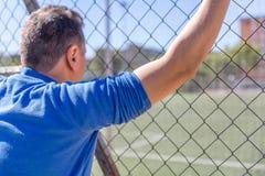 Fan jego drużyn futbolowych spojrzenia przy boiskiem piłkarskim od ogrodzenia obraz stock