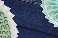 The fan of a lot of euro bills is on a dark denim surface. Backg. Round image royalty free stock image