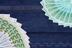 The fan of a lot of euro bills is on a dark denim surface. Backg. Round image royalty free stock images