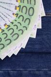 The fan of a lot of euro bills is on a dark denim surface. Backg. Round image stock photo