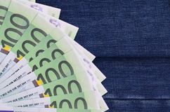 The fan of a lot of euro bills is on a dark denim surface. Backg. Round image royalty free stock photos
