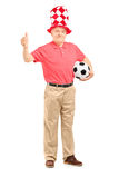 Fan mûre heureuse avec le chapeau tenant un ballon de football et donnant un thu Photo libre de droits