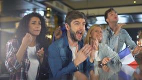 Fan macha francuz flagę, ogląda sporta program w barze, spęczenie o przegrywającej grą zbiory wideo