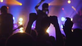 Fan macha ich ręki przy rockowym koncertem w noc klubie na pięknych złotych światłach w purpurowi kolory obraz stock