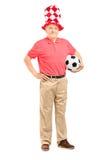 Fan madura con el sombrero que sostiene un balón de fútbol Fotos de archivo