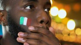 Fan maschio nero con la bandiera italiana sul ribaltamento della guancia circa il gioco perdente del gruppo favorito stock footage