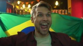 Fan masculina emocionada que agita la bandera brasile?a en la barra, victoria del equipo de deportes que disfruta metrajes