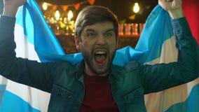 Fan masculina emocional que agita la bandera de la Argentina, victoria nacional del equipo de deportes que disfruta almacen de video